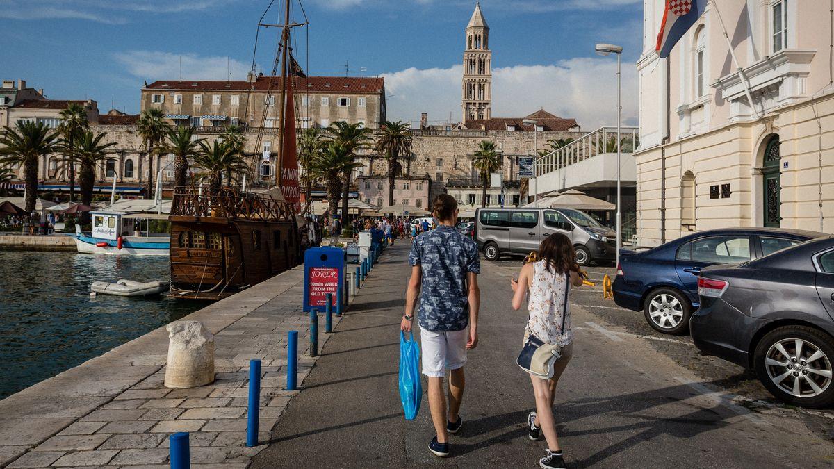 Kroatien, Split: Zwei Touristen gehen am Hafen entlang.