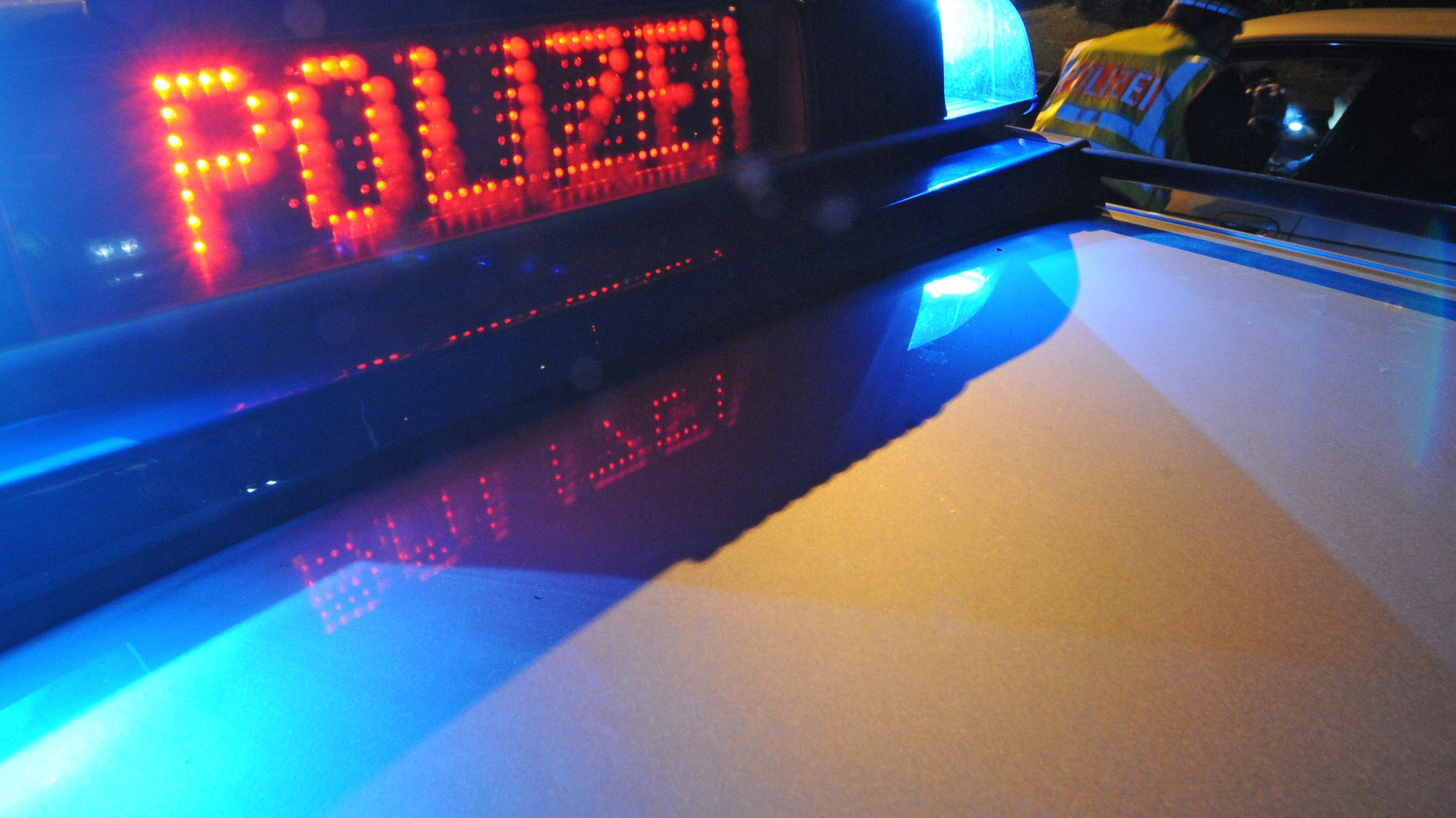 """Blaulicht und Leuchtschriftzug """"Polizei"""" auf einem Streifenwagen. Ein Polizeibeamter im Hintergrund. (Archivbild)"""