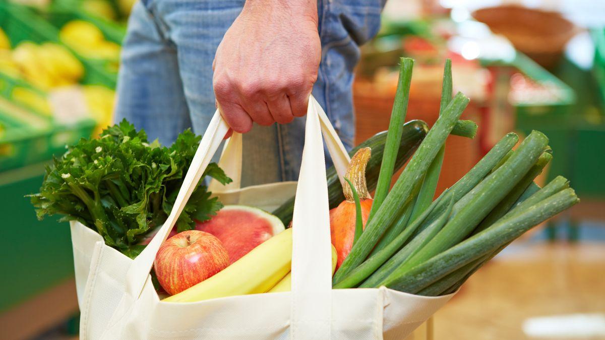 Ein Mann mit einer Leinen-Einkaufstasche, die mit Obst und Gemüse gefüllt ist.