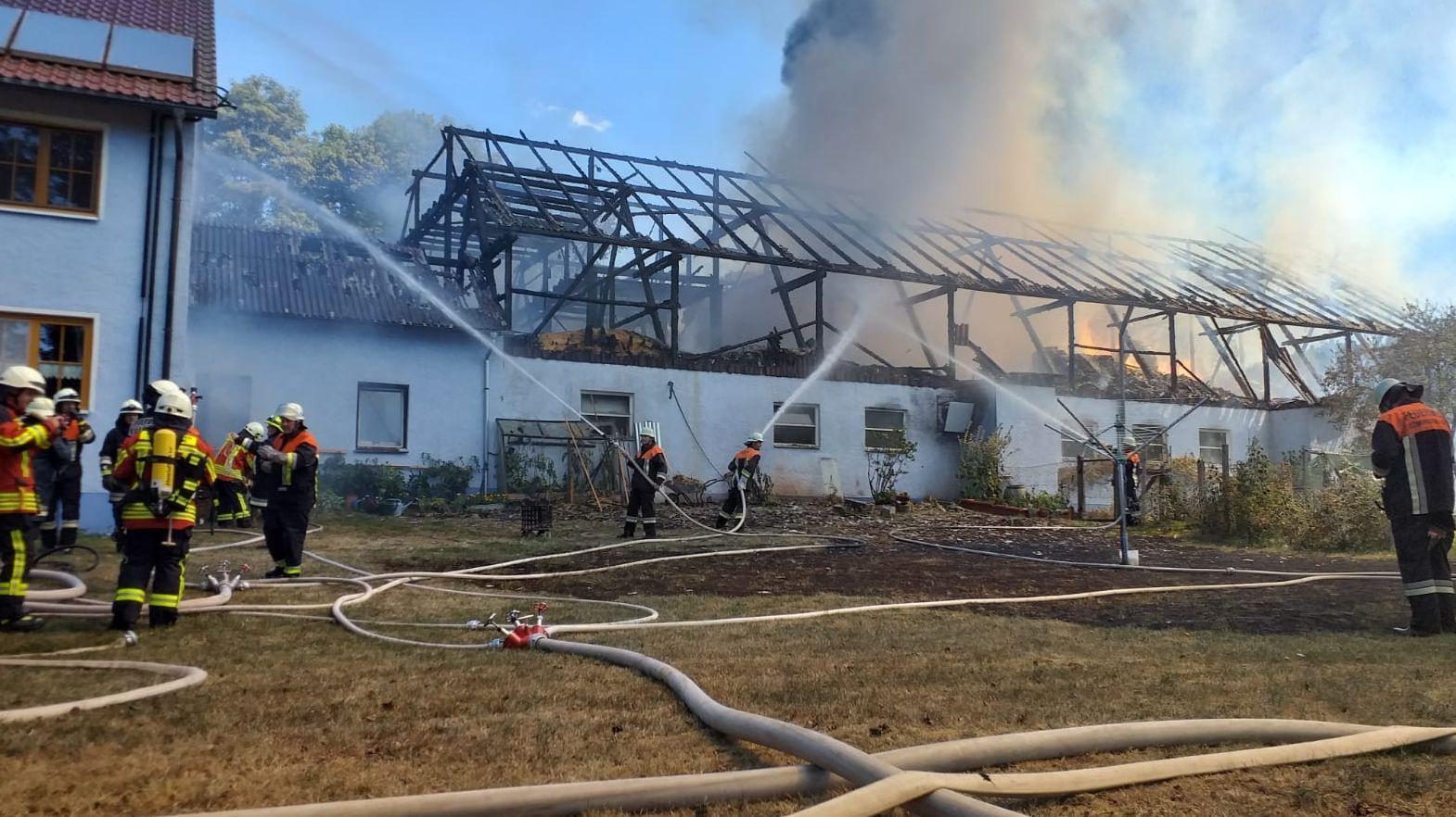 Die Feuerwehr löscht den Stall, dessen Dach nur noch ein Gerippe ist