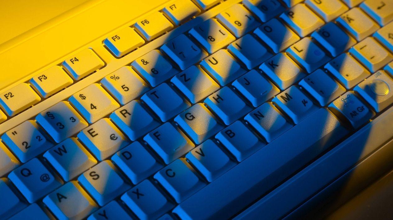 Der Schatten einer Hand schwebt über einer Tastatur