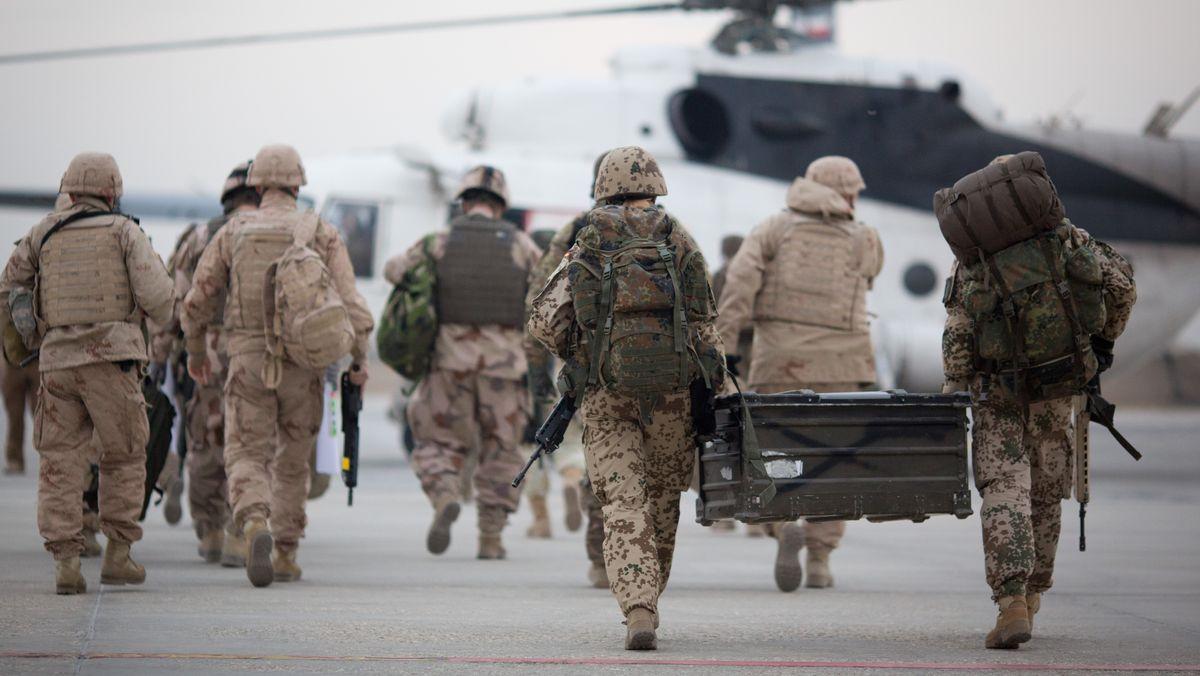 Bundeswehrsoldaten tragen auf dem Flughafen in Masar-i-Scharif zu einem wartenden Hubschrauber eine Feldkiste. Soldaten anderer Nationen begleiten das Team.