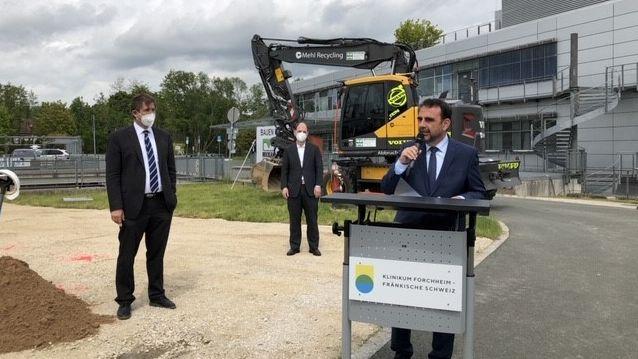 Gesundheitsminister Klaus Holetschek spricht in ein Mikrofon, im Hintergrund ein Bagger und ein Klinikgebäude.