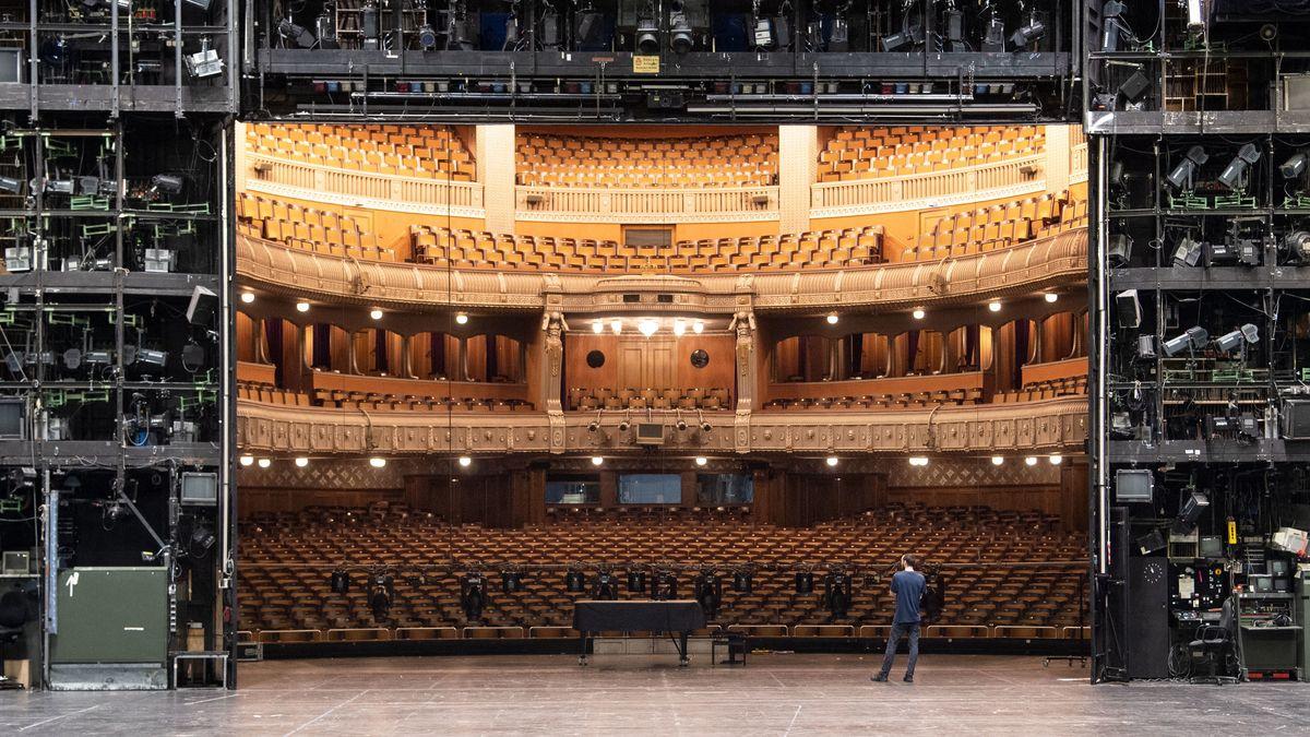 Ein Mann steht allein auf einer Bühne vor einem leeren Saal.