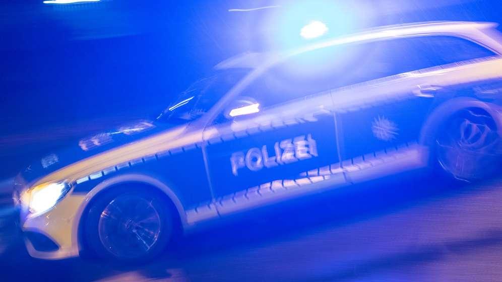 Ein blaues Polizeiauto fährt nachts mit Blaulicht (Symbolbild).   Bild:picture-alliance/dpa