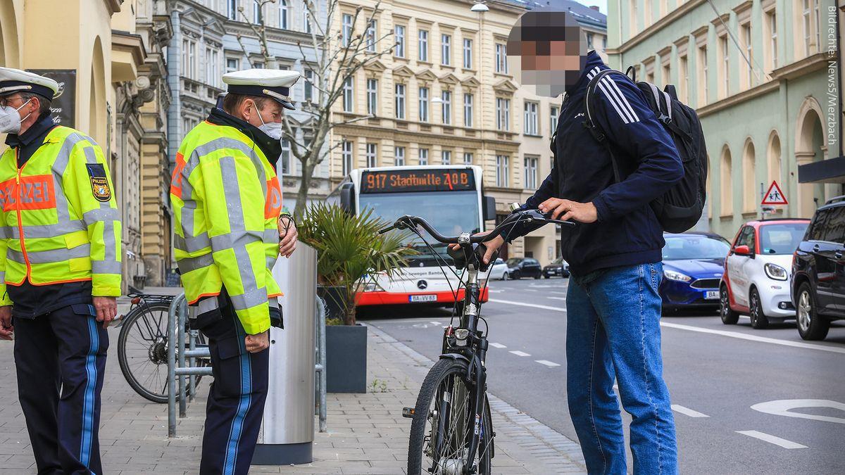 Ein Polizist kontrolliert in Bamberg einen Fahrradfahrer, dahinter ein Bus und parkende Autos.