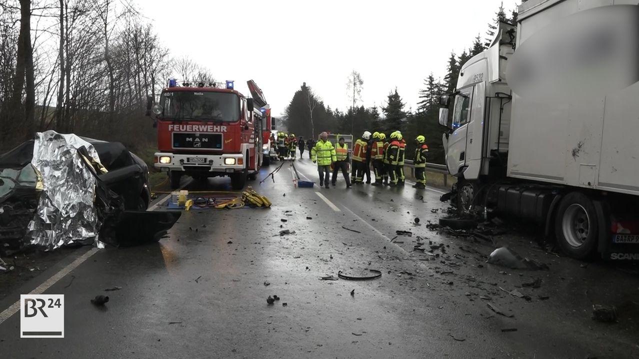 Ein stark zerstörtes Autowrack und ein Lastwagen mit Unfallschaden stehen auf der Bundesstraße B173, auf der viele Trümmer liegen. Im Hintergrund stehen ein Feuerwehrfahrzeug sowie mehrere Kräfte der Feuerwehr.