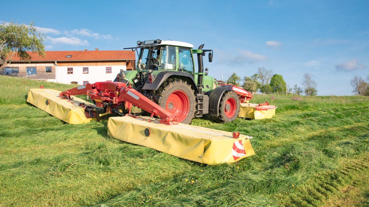 Traktor mit zwei angehängtem Mähwerken und eines im Frontbereich an einem sonnigen Frühlingstag beim Mähen von Gras für Silage.