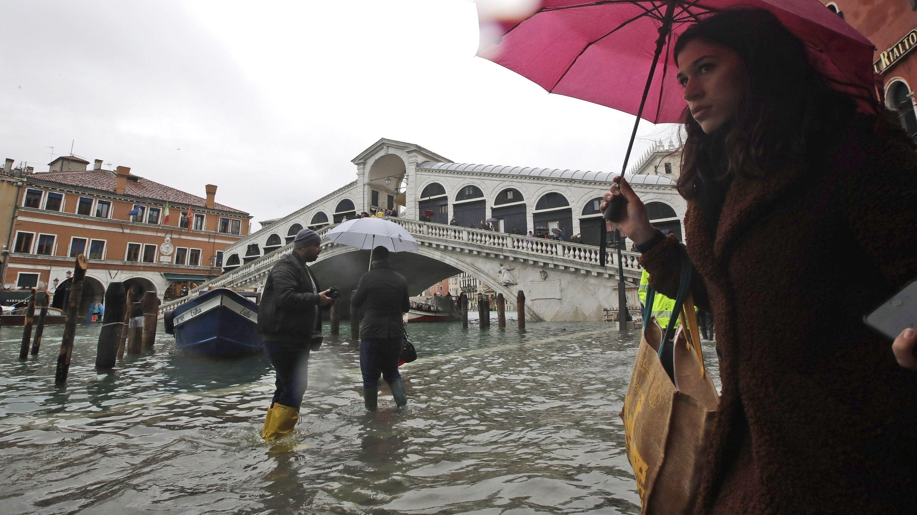 Passanten gehen in der Nähe der Rialto-Brücke durch das Hochwasser.