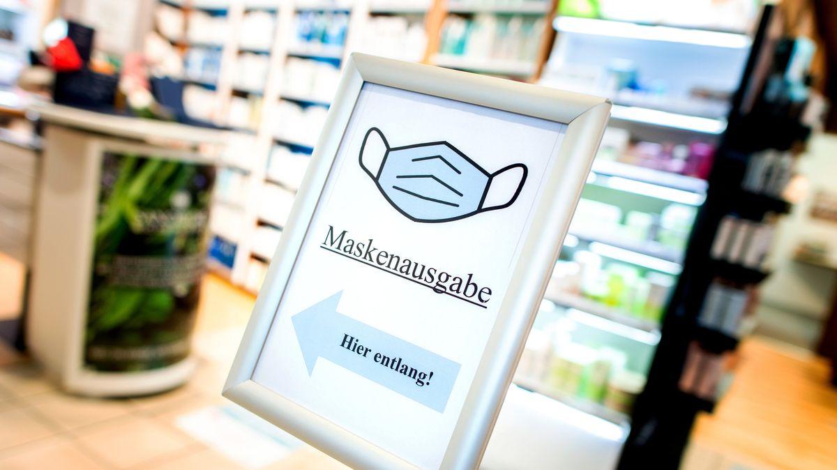 """Ein Schild mit der Aufschrift """"Maskenausgabe"""" steht im Eingang einer Apotheke"""