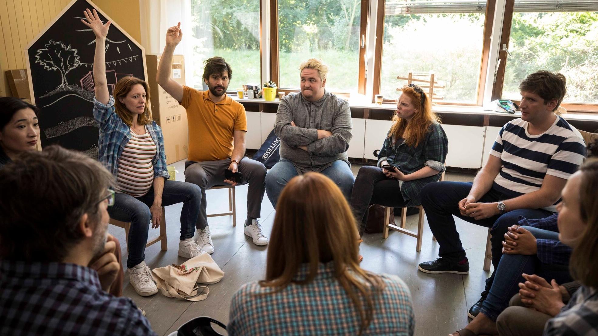 """Szene aus """"Andere Eltern"""": Eltern sitzen im Stuhlkreis in einer KiTa"""