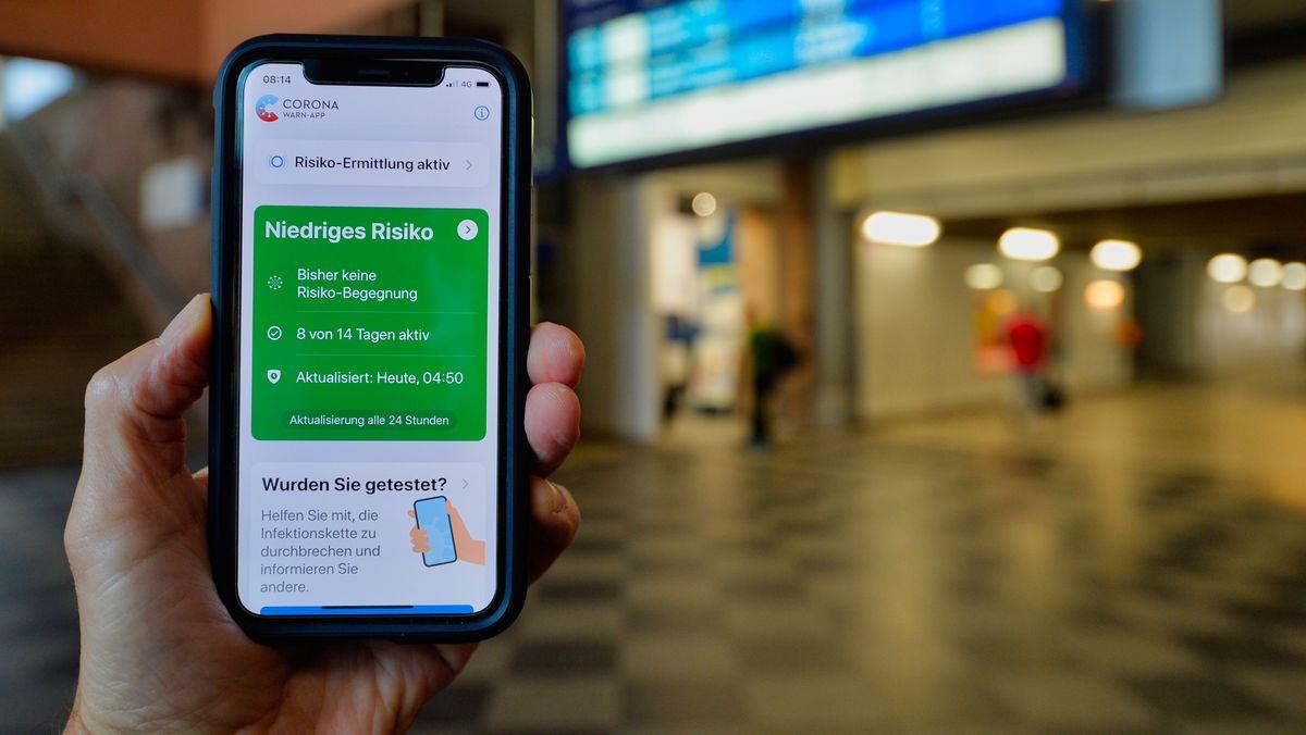"""Corona-Warn-App auf iPhone zeigt einer Person in einem Bahnhof die Mitteilung """"Niedriges Risiko"""""""