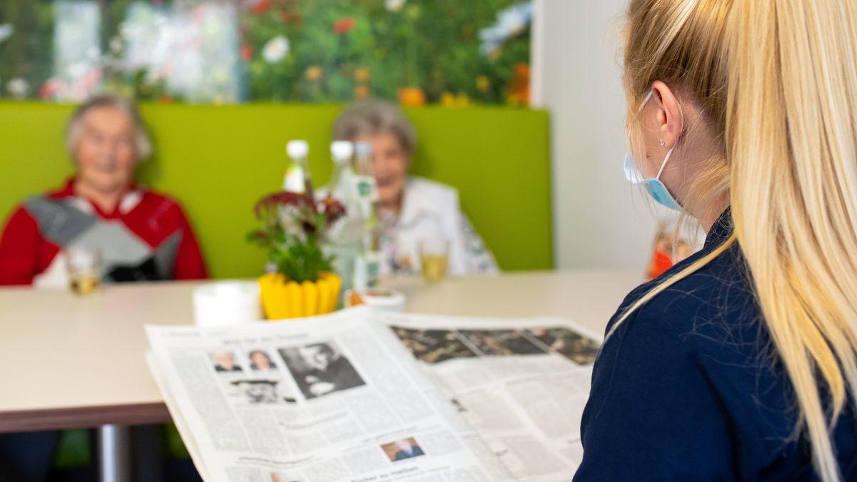 Eine Altenpflegerin eines Altenheims liest Bewohnerinnen an einem Tisch aus einer Zeitung vor.