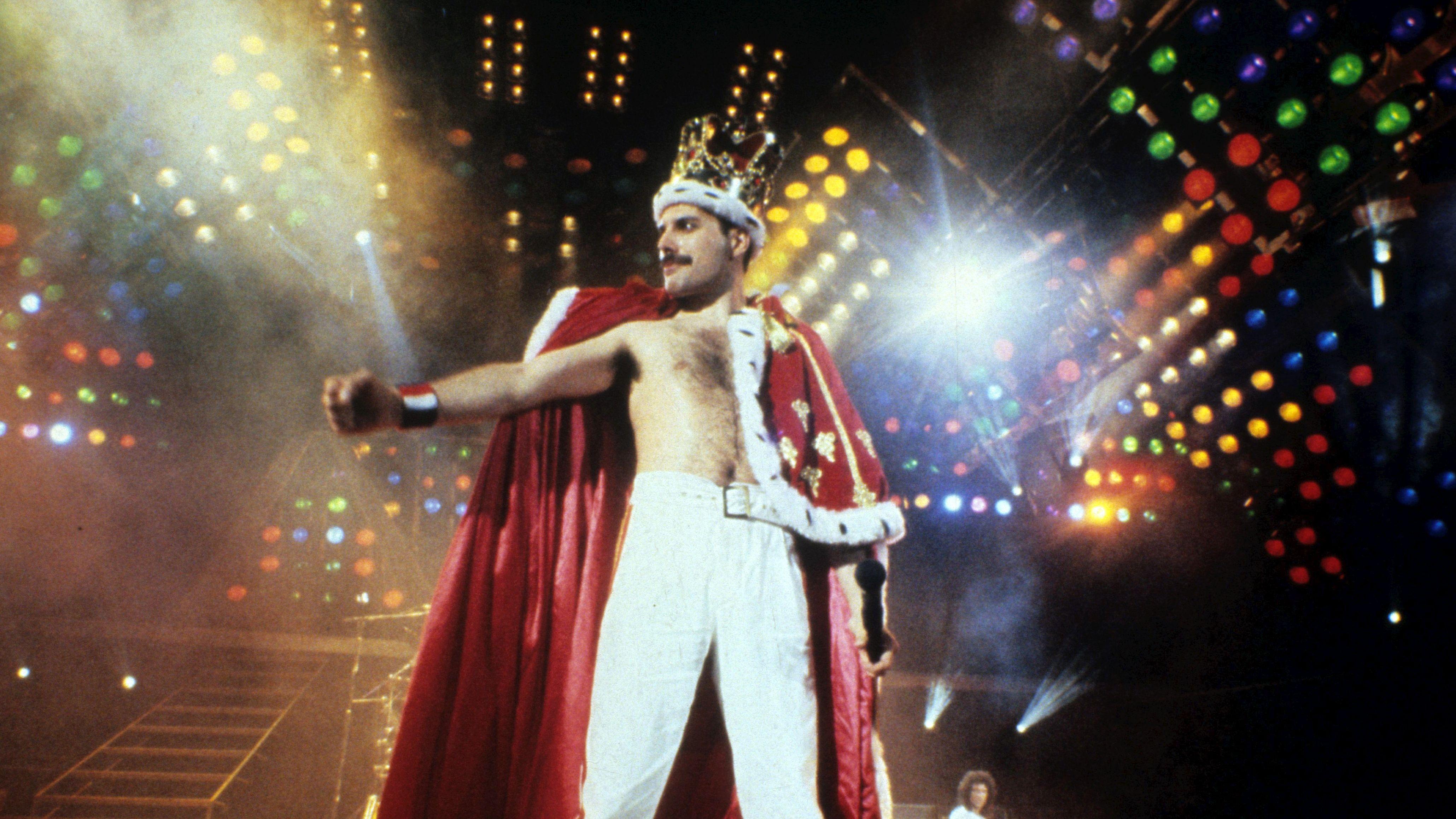 Freddie Mercury auf der Bühne, trägt eine Krone, einen roten Mantel und eine weiße Hose.