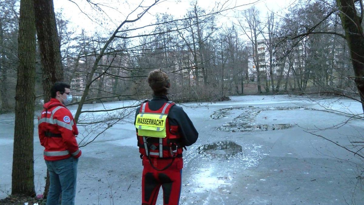 Mitarbeiter von Wasserwacht und BRK am Ufer eines vereisten Weihers.