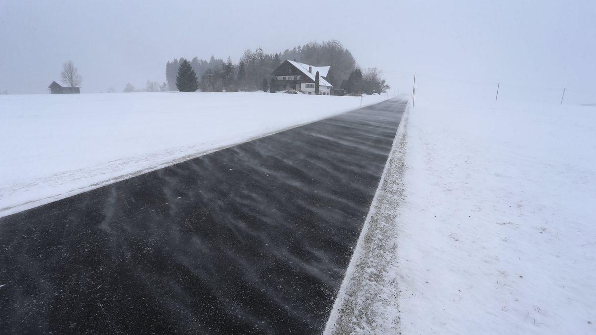 Schnee wird von heftigen Windböen über eine Landstraße geweht