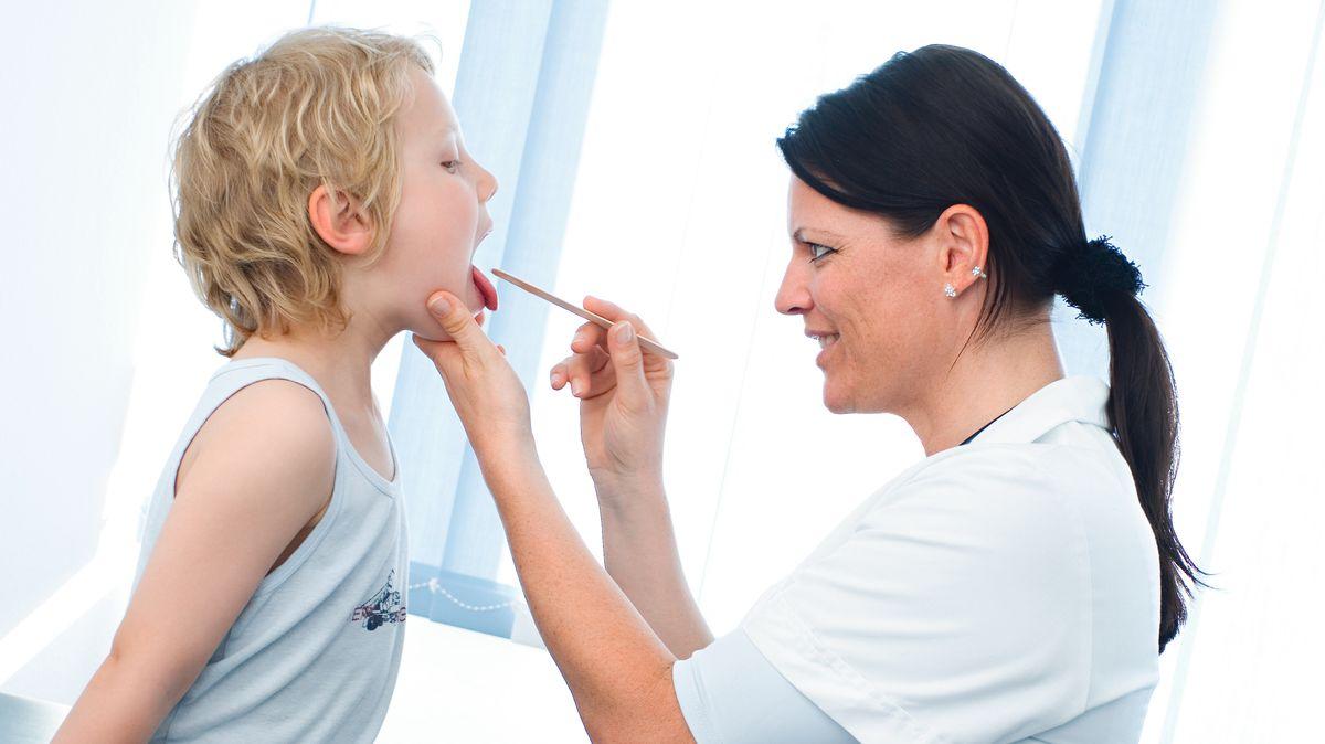 Kinderärztin schaut Jungem in den Rachen