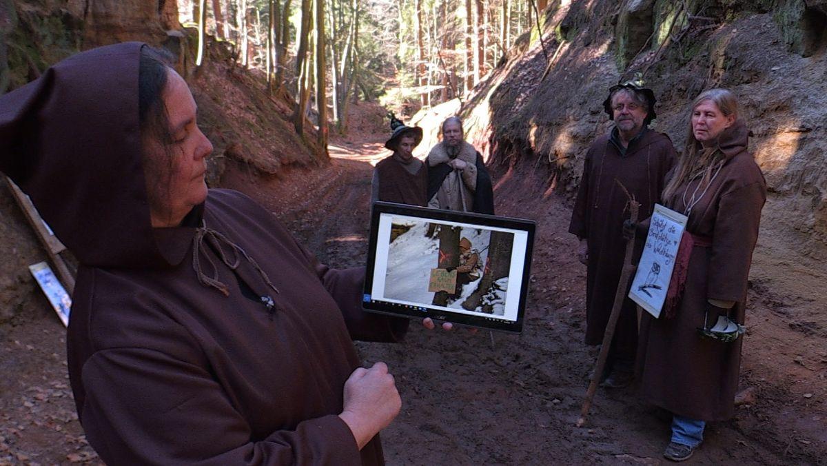 Menschen in Kostümen zeigen Bilder auf einem Tablet-Computer.