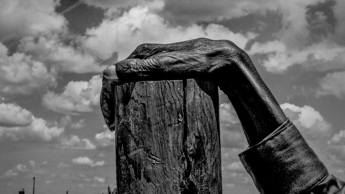 Alte Hand auf Holzpfahl