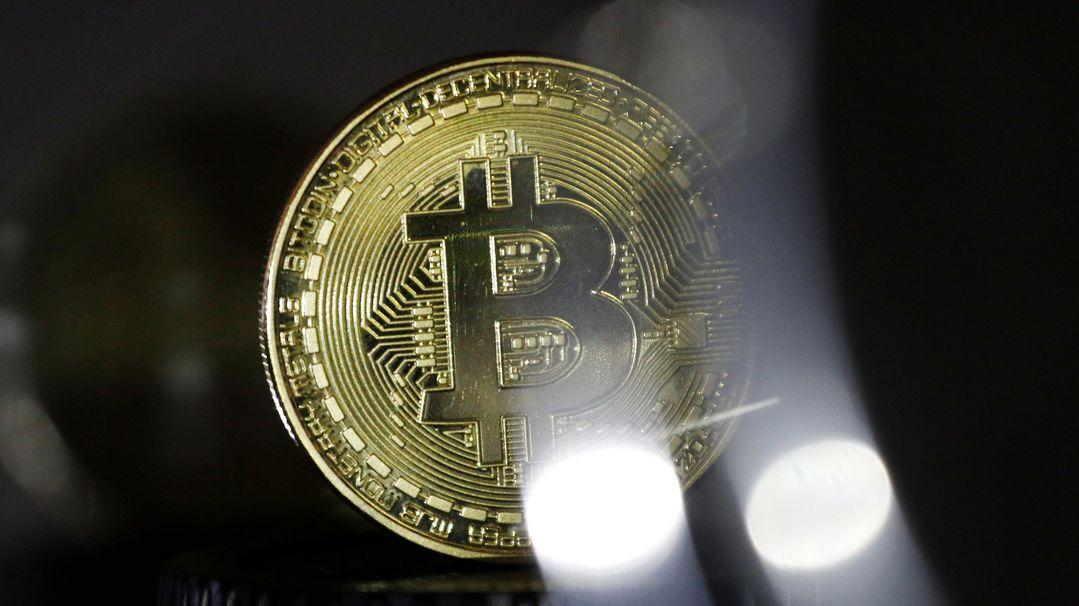 Eine Bitcoin Münze wird präsentiert (gestellte Szene).