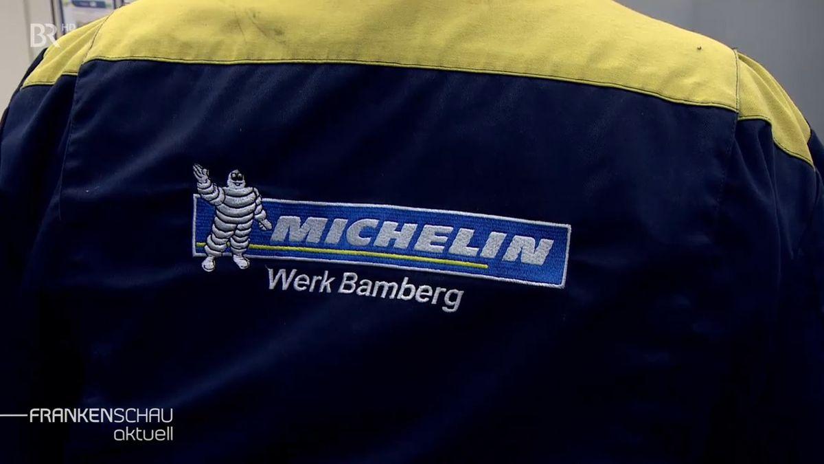 Ein Mitarbeiter trägt eine Jacke, auf der ein blaues Schild aufgenäht ist, das einen weiße Michelin-Figur zeigt, darunter ist zu lesen: Werk Bamberg.