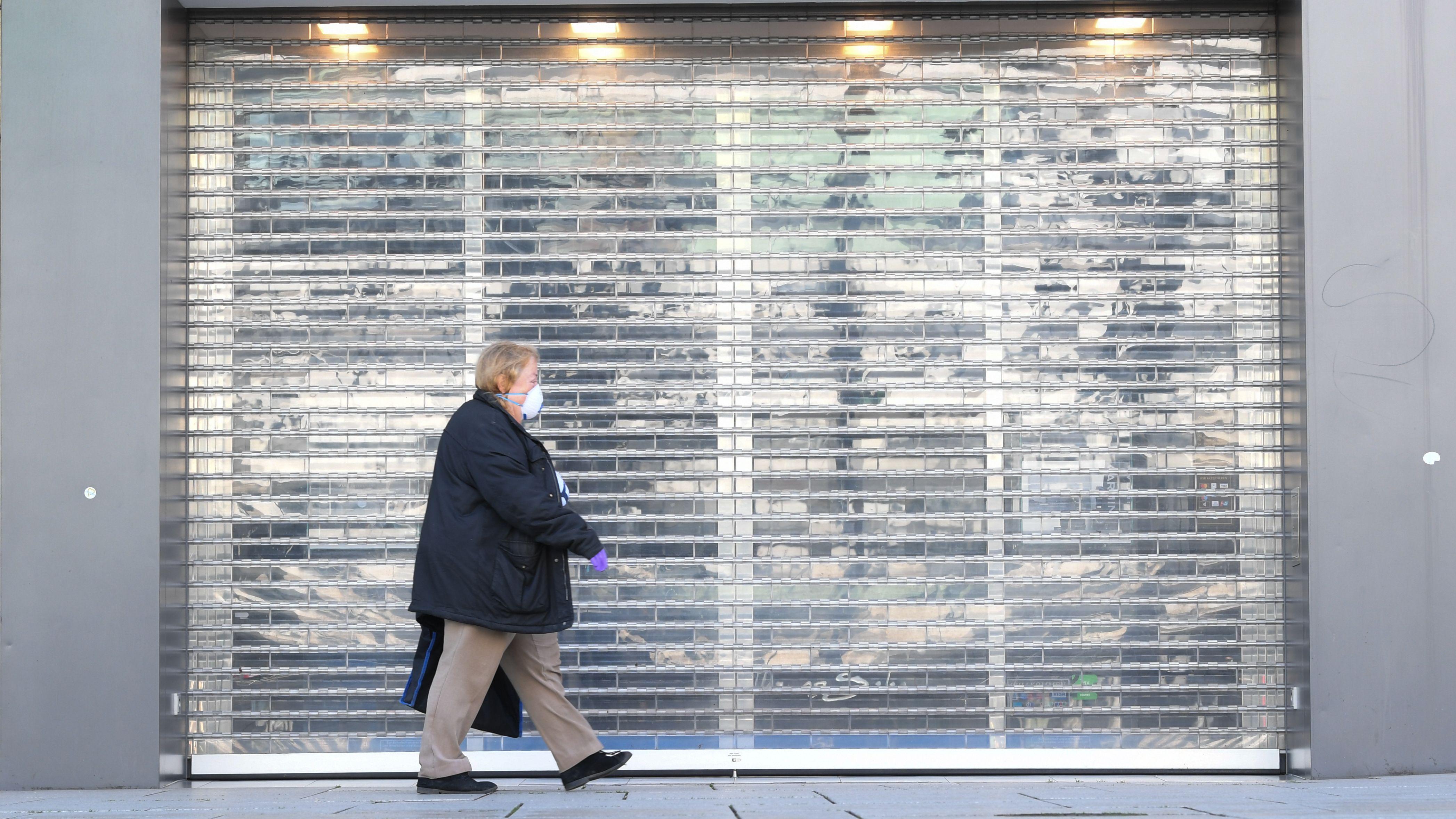 Eine Frau mit Schutzmaske geht auf der Frankfurter Einkaufsmeile Zeil an einem Juweliergeschäft vorbei, an dem das Rollgitter heruntergelassen ist. Wegen der Ausbreitung des Coronavirus bleiben jetzt auch Kneipen, Kinos, Bordelle, Theater, Museen, Diskotheken und viele Läden geschlossen.