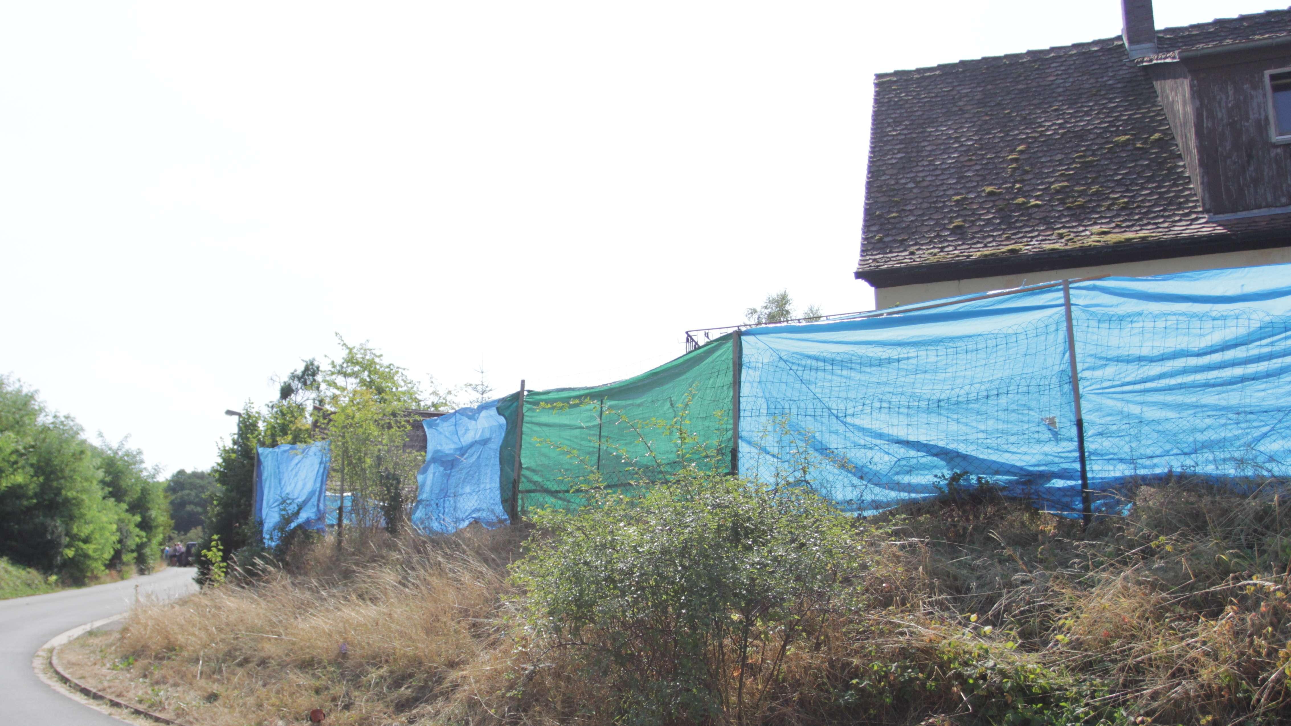 Mit Planen verhüllter Zaun vor einem Haus