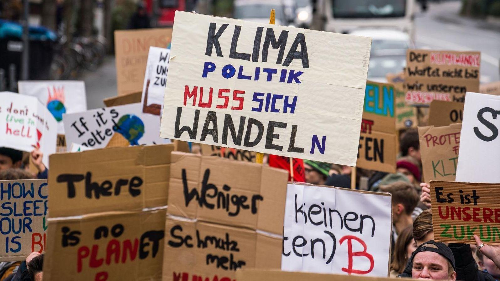 Demonstranten halten Plakate in die Höhe auf denen Parolen zum Klimaschutz stehen.