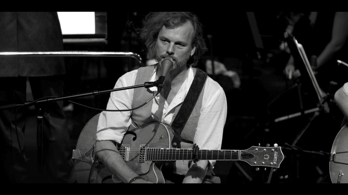 Gerd Baumann mit Gitarre und Gesangsmikrofon bei einem Auftritt