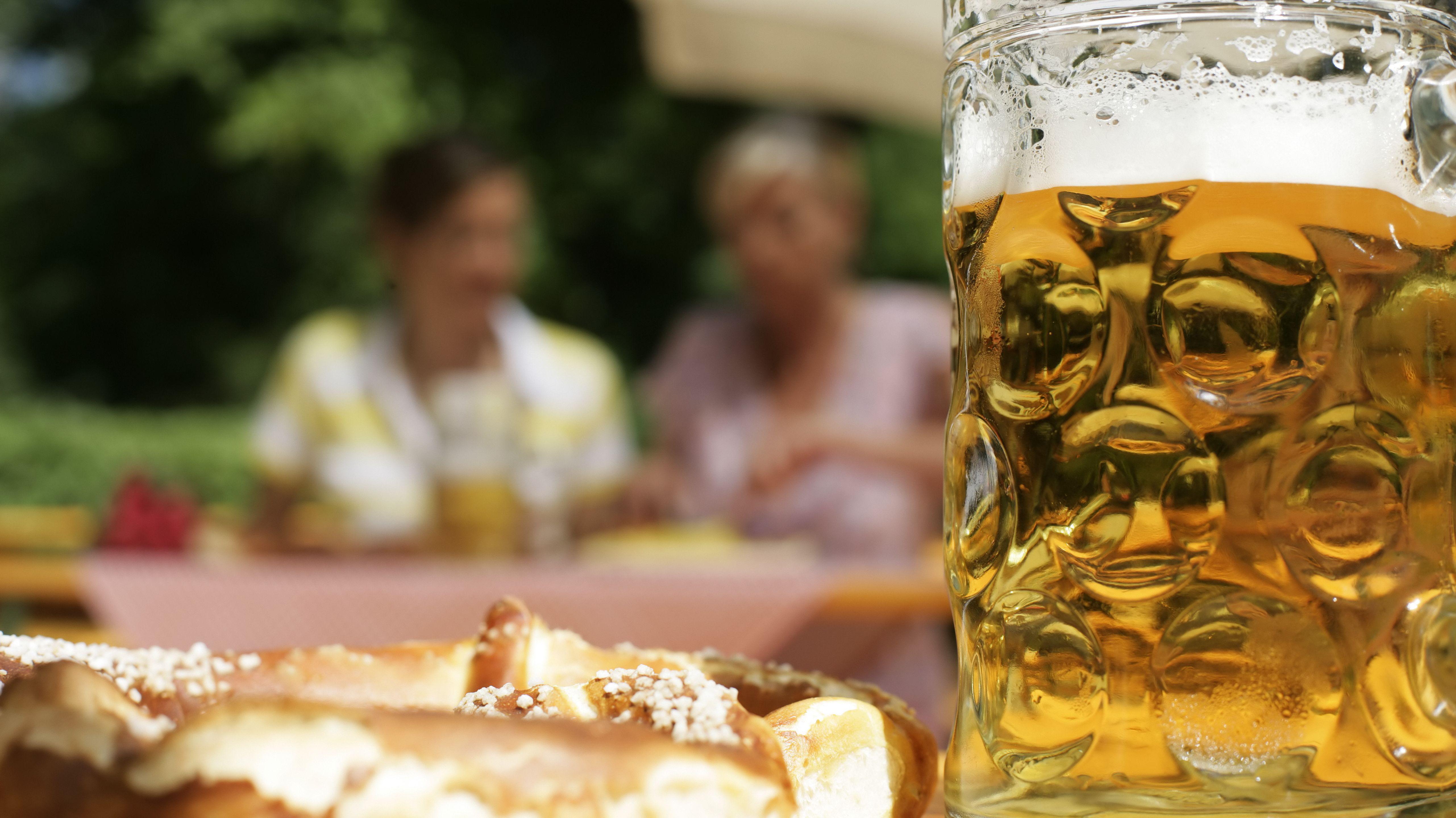 Eine große Breze und eine Mass Bier auf einem Wirtshaustisch unter freiem Himmel