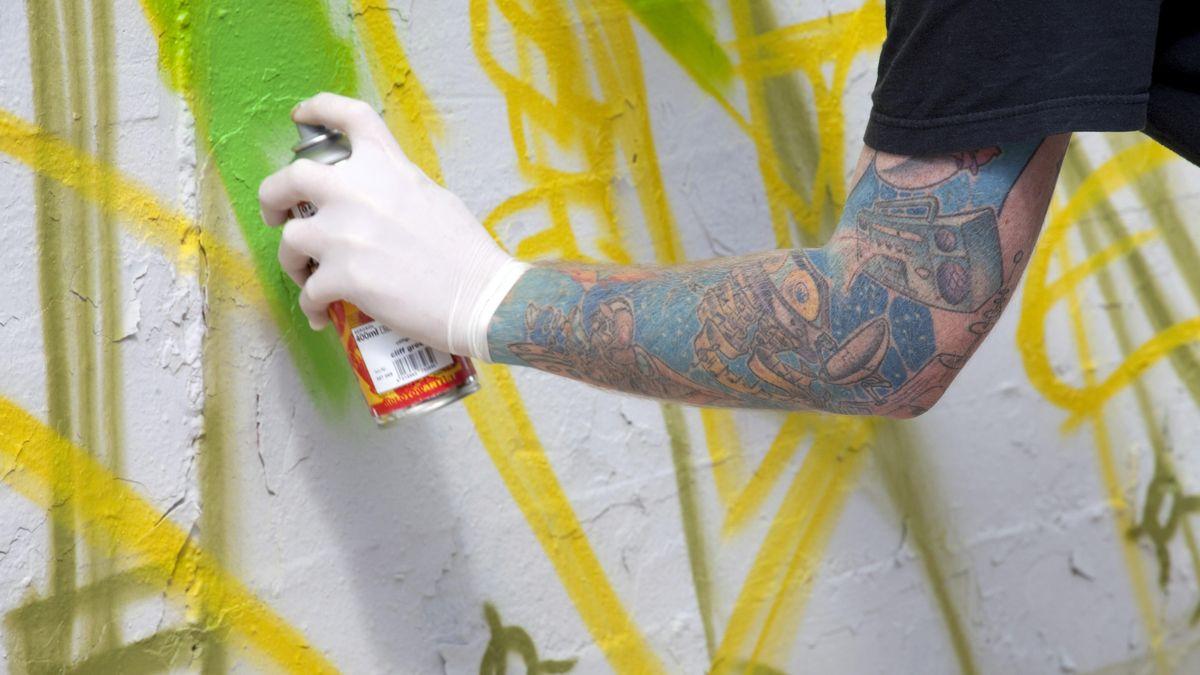 Ein Arm mit Gummihandschuh und einer Spraydose vor einer bemalten Wand.