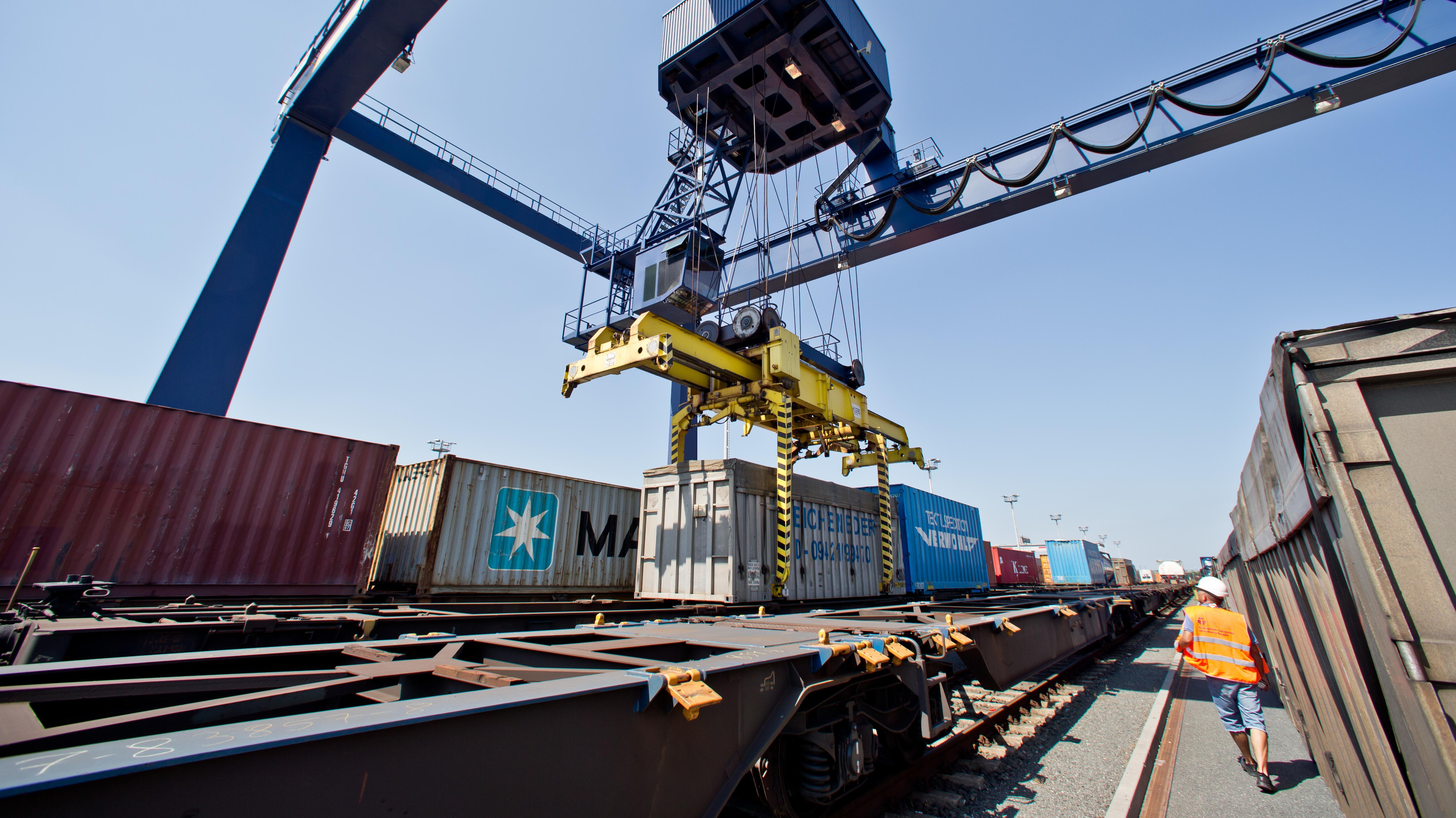 Mit einem Kran werden am Hafen in Nürnberg Frachtcontainer auf die Schiene verladen.