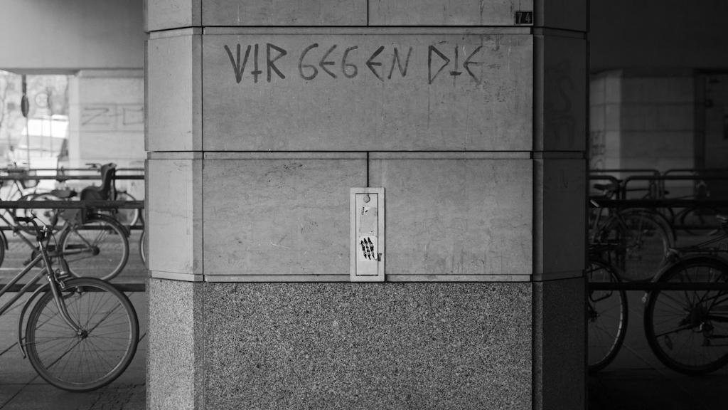 """Filmstill aus """"Heimat ist ein Raum aus Zeit"""": Schriftzug """"Wir gegen die"""" auf einer Mauer, Fahrräder in einem Durchgang"""