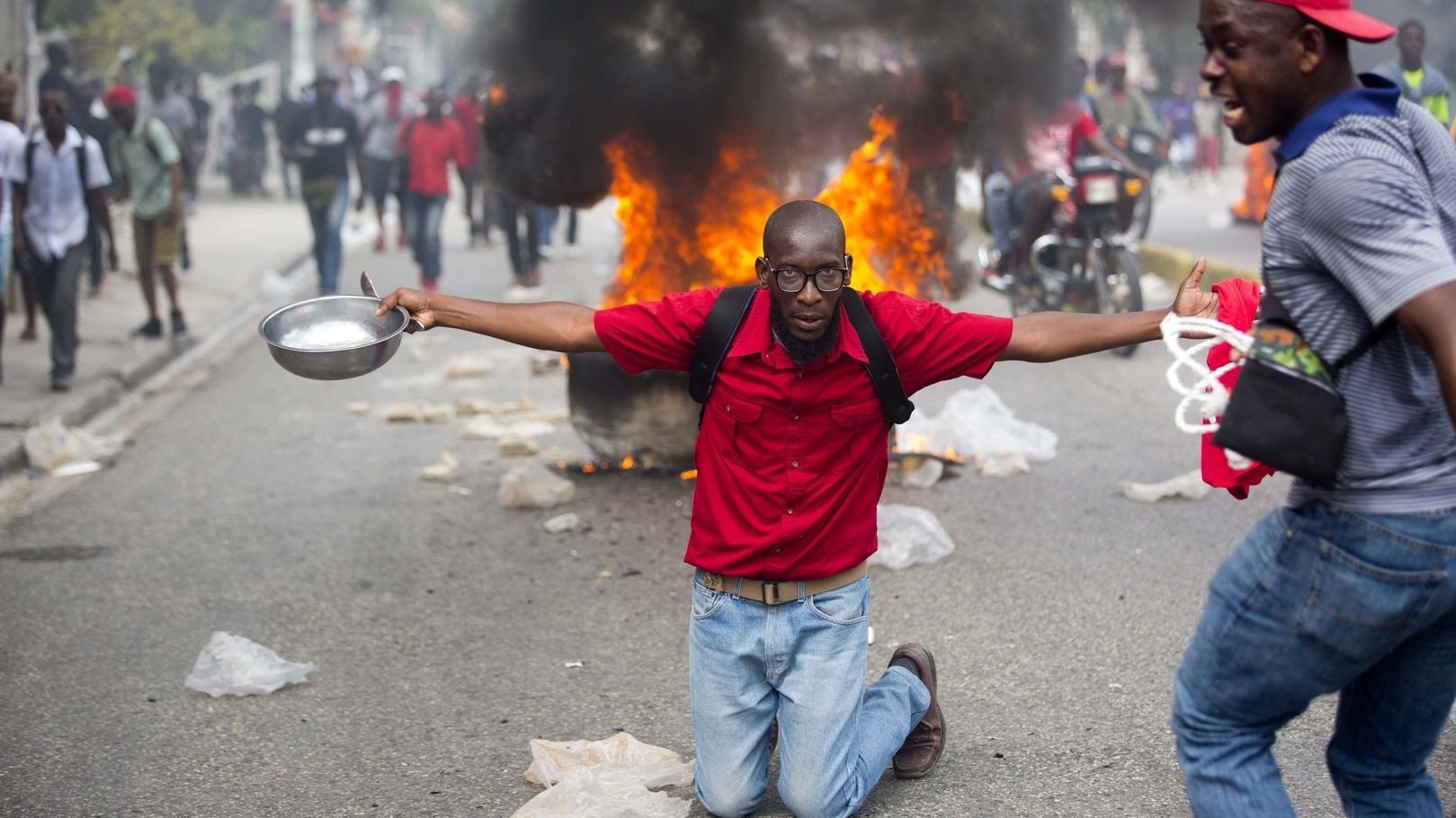 Ein Demonstrant kniet vor einem Feuer auf einer Sraße, breitet seine Arme aus und hält einen Schüssel und einen Löffel.