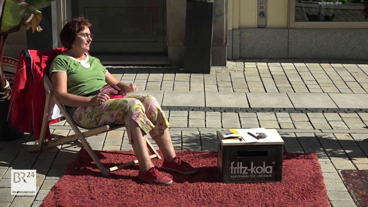 Eine Frau sitzt in einem Liegestuhl, die Füße auf einem roten Teppich, der auf der Straße ausgebreitet ist.