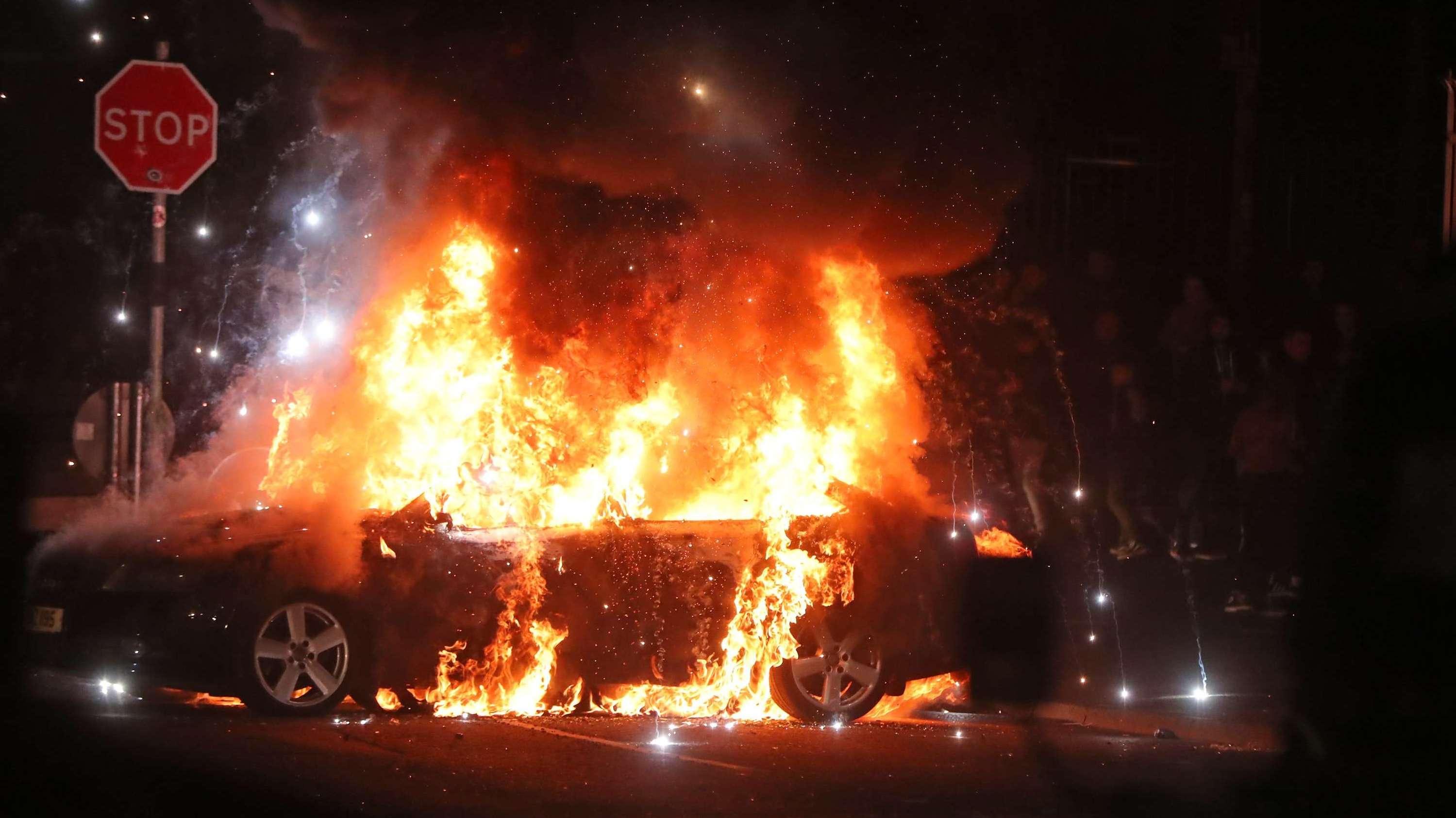 Ein Auto brennt während sozialer Unruhen