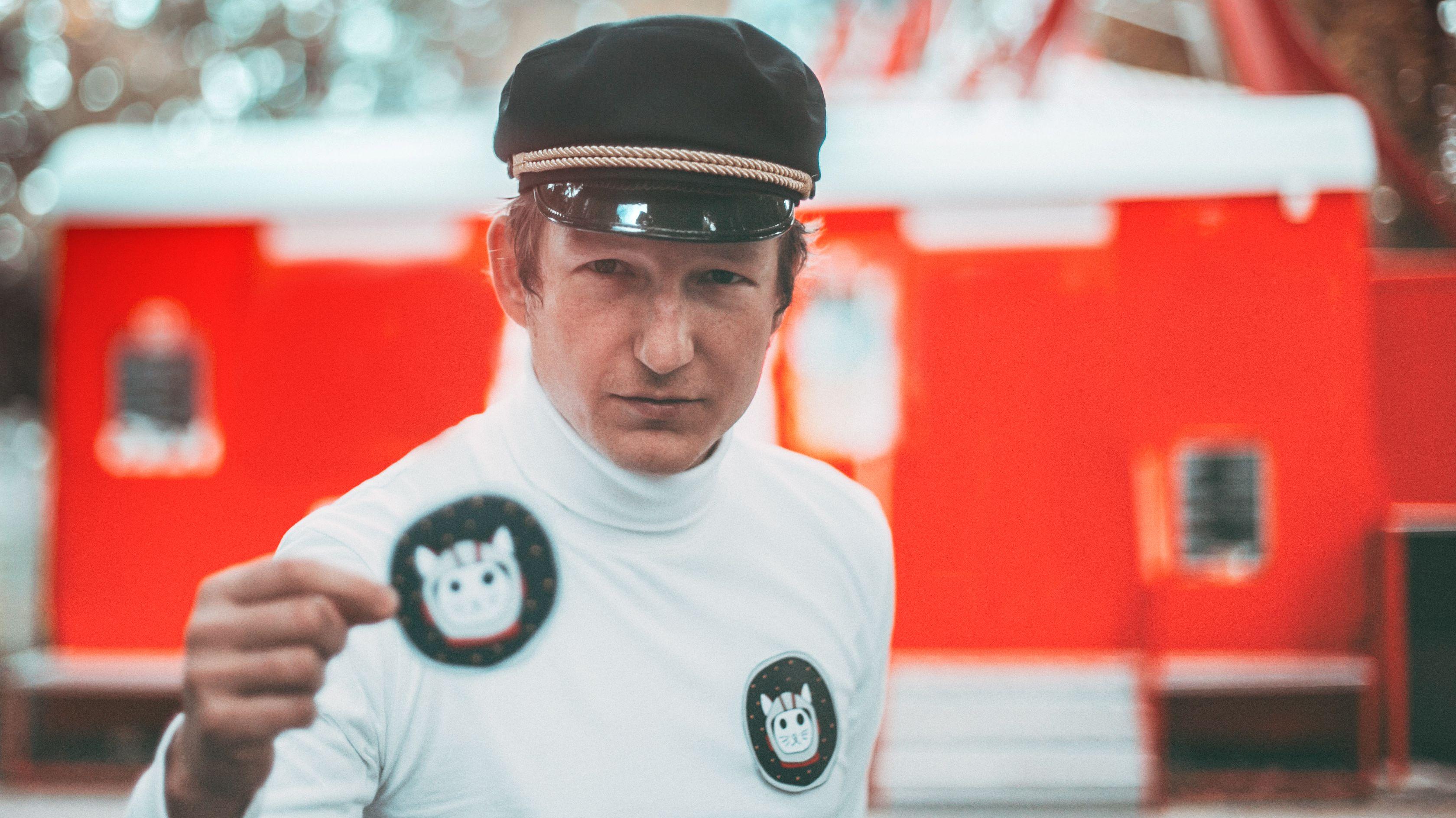 Sänger pauT mit Kapitänsmütze, weißem Rolli und Weltraumkatzen-Stickern, im Hintergrund ein knallroter Bauwagen