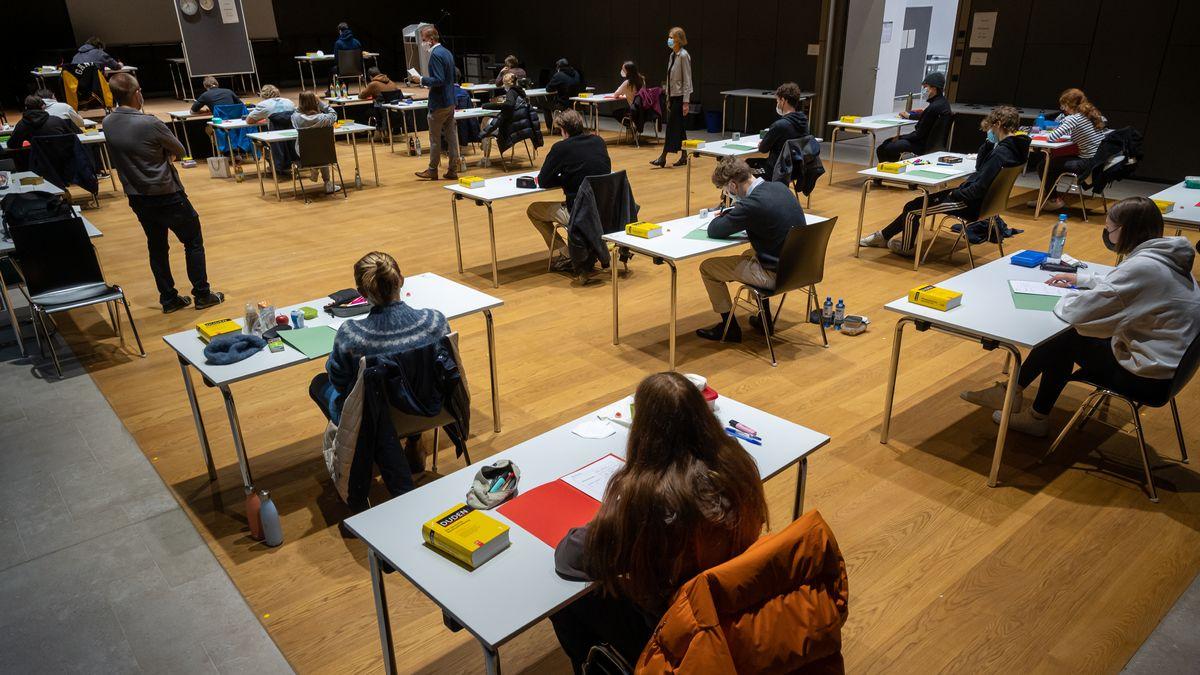 Schüler sitzen unter der Aufsicht mehrerer Lehrer in einer Aula um eine Prüfung abzulegen.