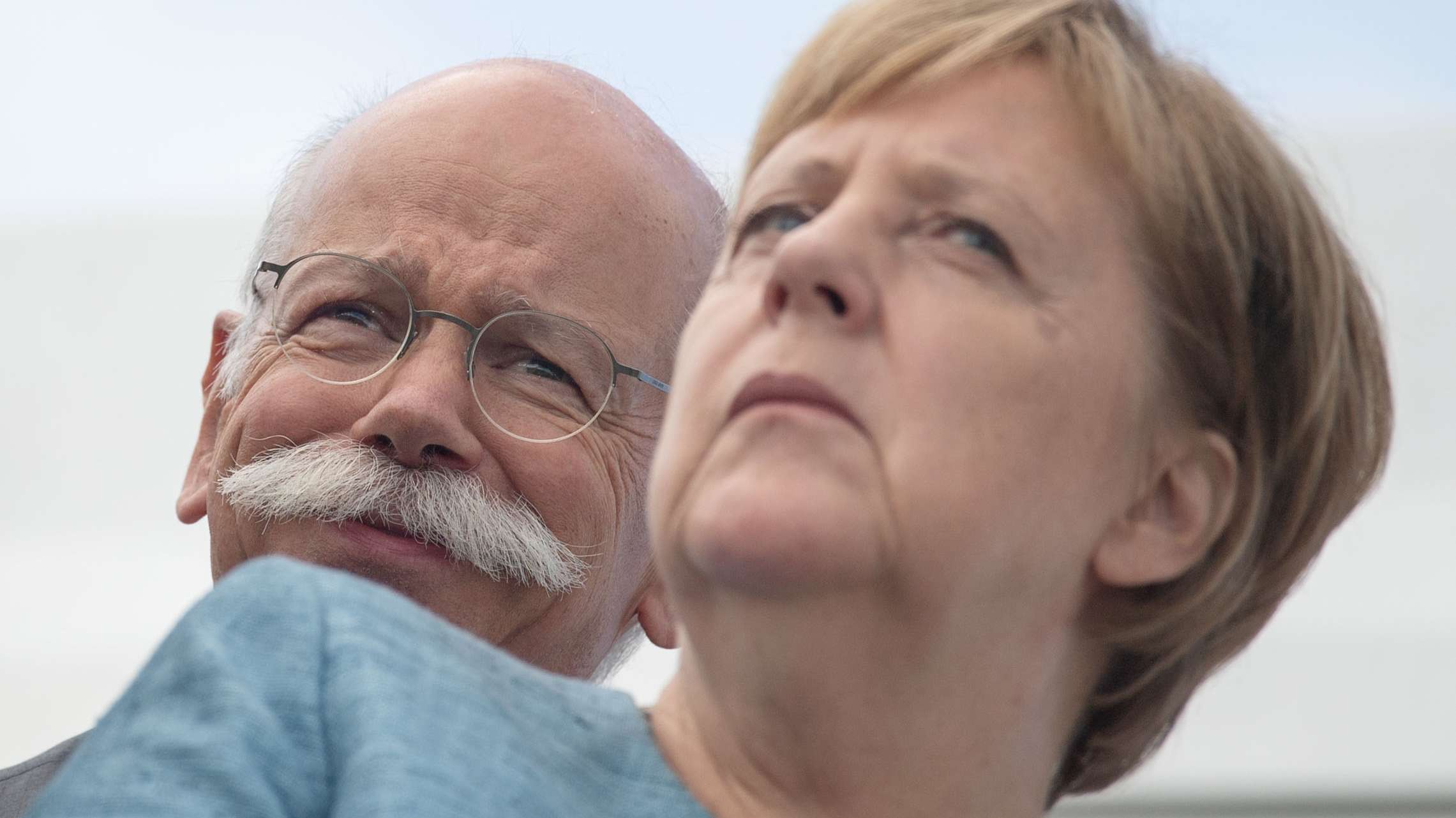 Daimler-Chef Zetsche steht lächelnd hinter Bundeskanzlerin Angela Merkel (Archivbild)