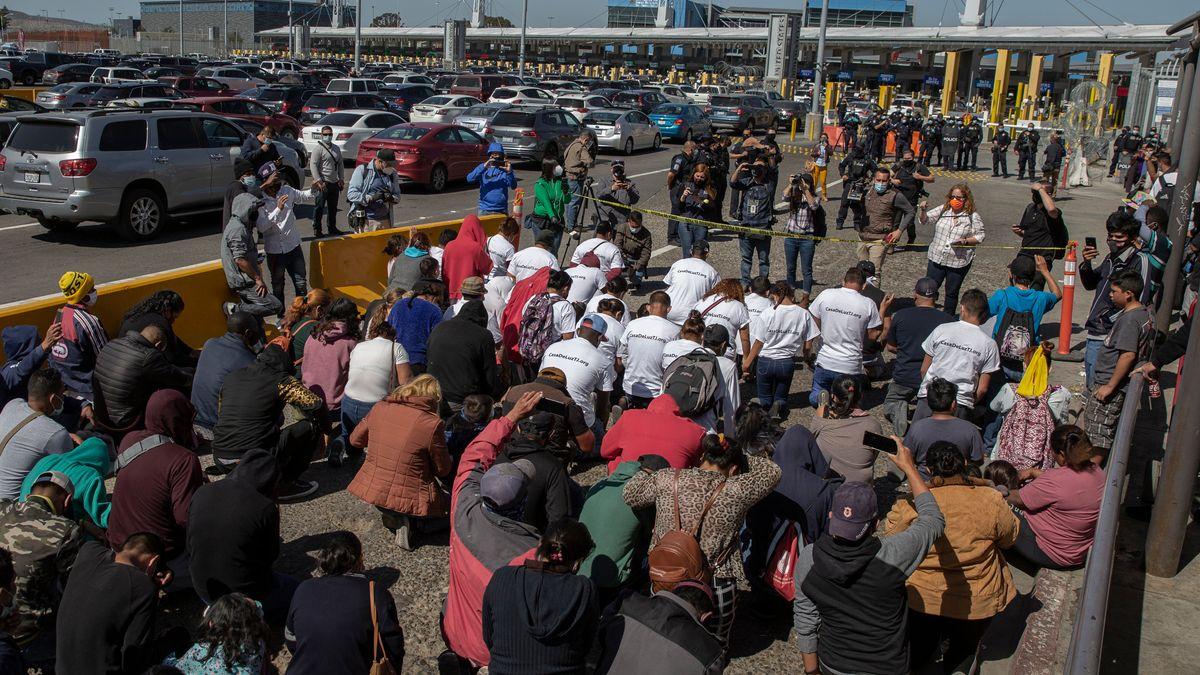 """Eine Gruppe Migranten, die T-Shirts mit der Aufschrift """"Biden, lass uns bitte rein"""" tragen, kniet Anfang März am Grenzübergang und betet."""