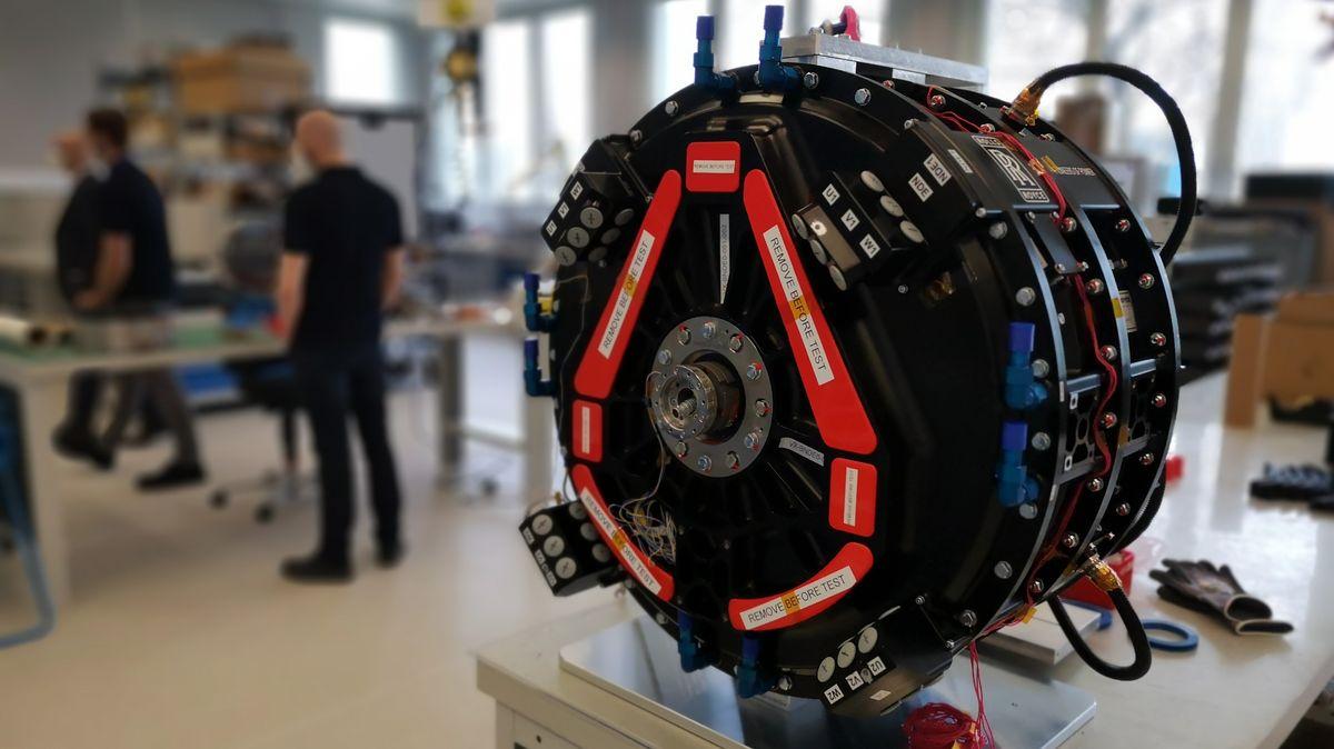 Foto eines Antriebs von Rolls Royce, der sich im Aufbau befindet, im Hintergrund Mitarbeitende mit Mundschutz.