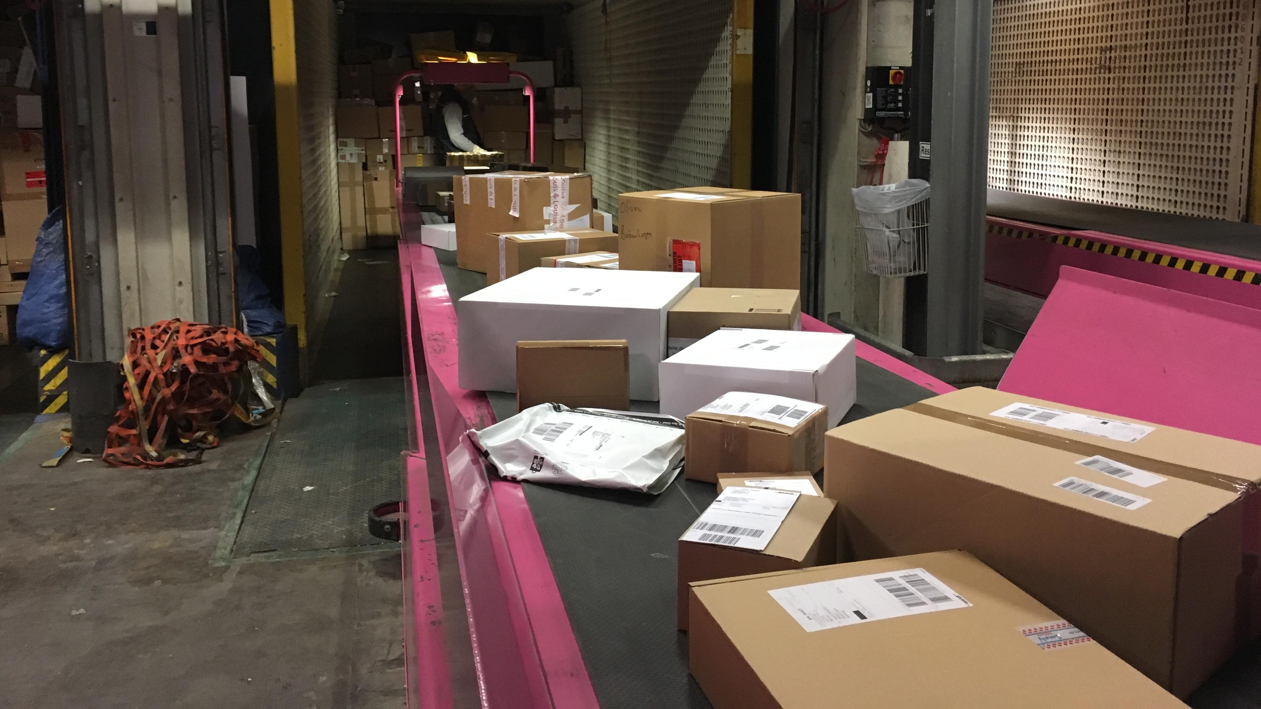 Die Pakete werden auf ein großes zentrales Förderband geschoben. Zwei Meter in der Sekunde legen die Pakete von nun an zurück.