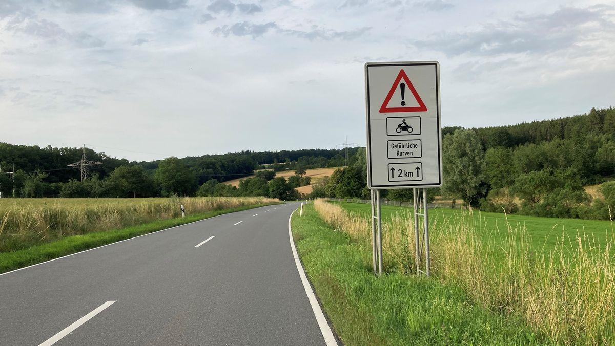 """Straße mit Schild """"Gefährliche Kurven"""""""
