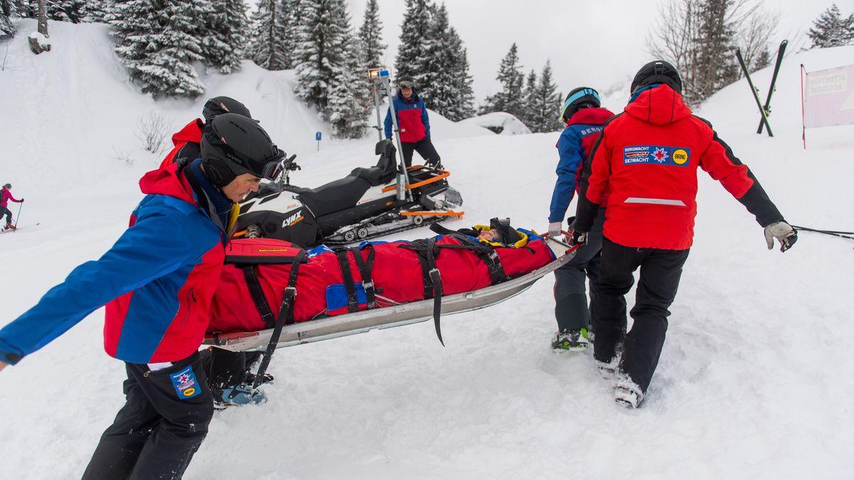 Mitglieder der Bergwacht helfen in einem Skigebiet in Garmisch-Partenkirchen einer verletzten Skifahrerin (gestellte Szene).