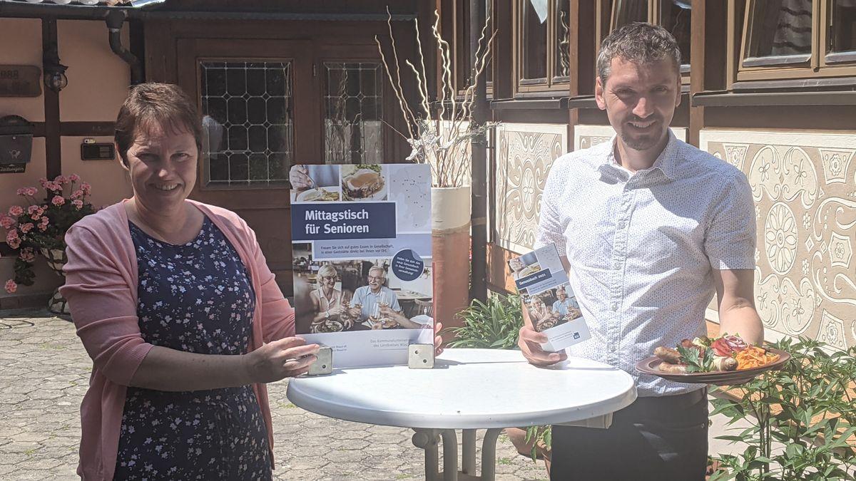 """Carmen Mayr und Tobias Konrad vom Kommunalunternehmen des Landkreises Würzburg bewerben den """"Mittagstisch für Senioren""""."""
