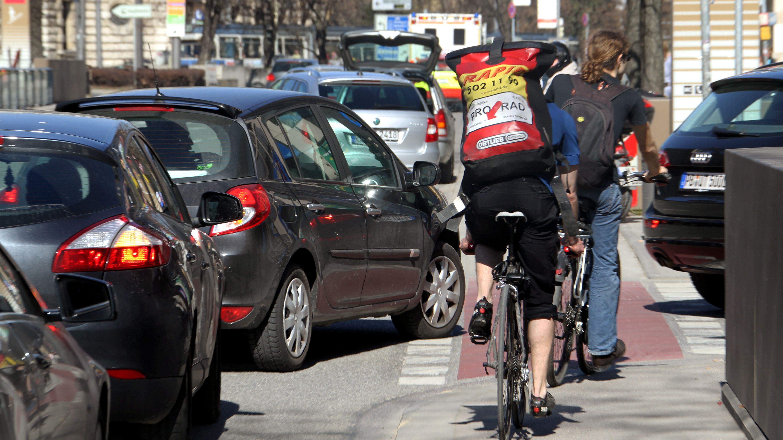 Radfahrer auf der Radspur und rechts abbiegende Autos.
