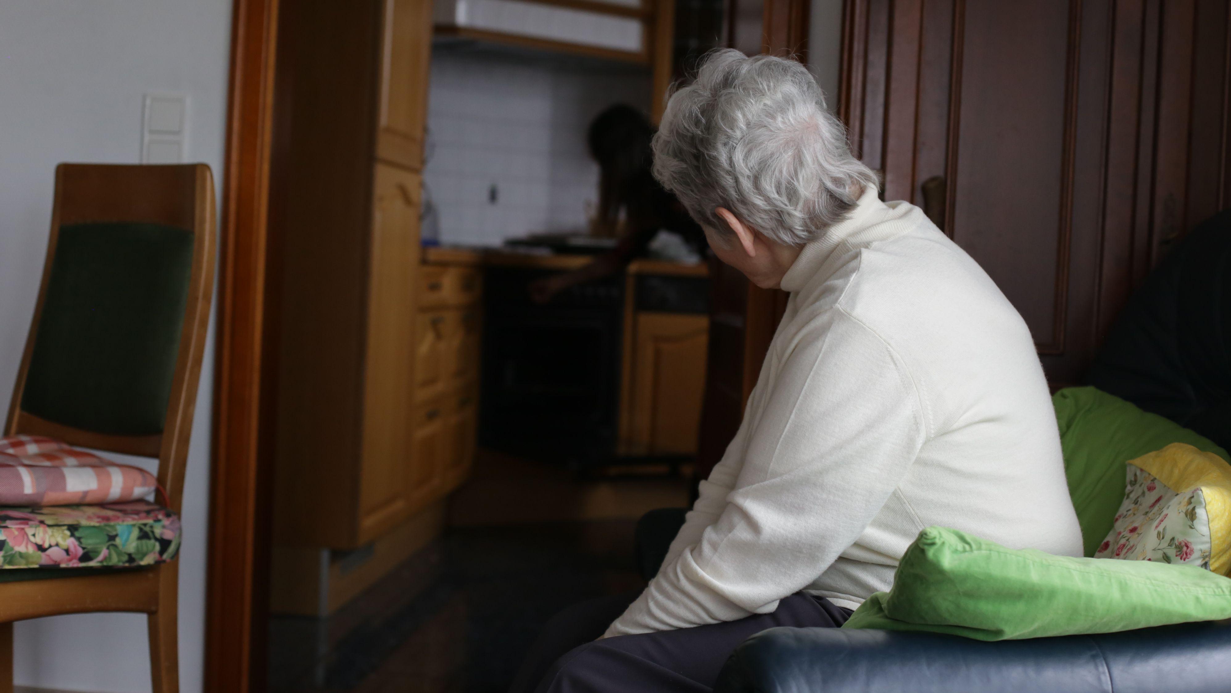 Eine Seniorin sitzt auf einem Sessel alleine in ihrer Wohnung.