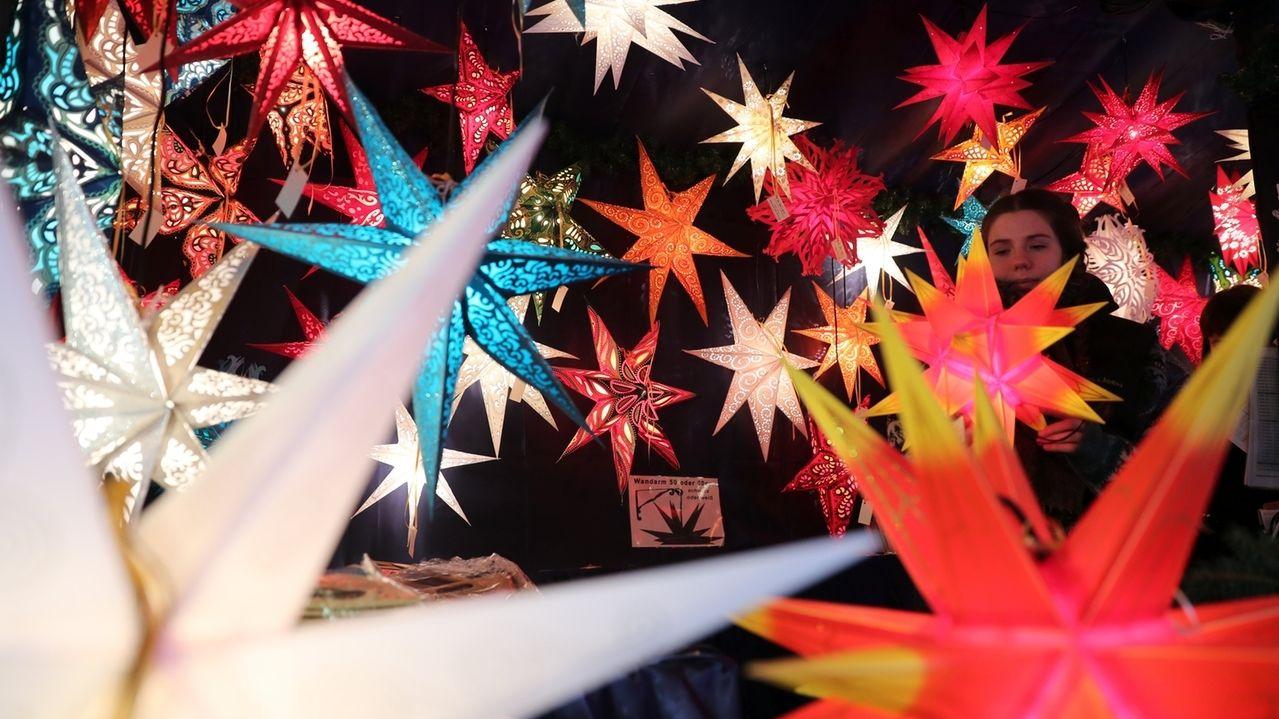 Bunte Sterne leuchten in einer Marktbude auf dem Christkindlesmarkt.