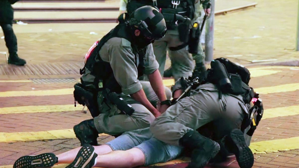 Uniformierte bedrängen einen Demonstranten