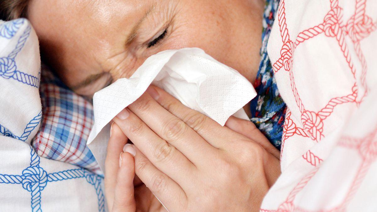 Eine Frau liegt im Bett und putzt sich die Nase.